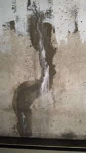Patched foundation crack with staining from minerals