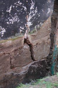 Broken cinder-block foundation wall with wide crack
