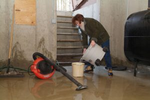 lady mopping up the water in her basement