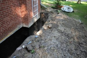 Excavated concrete block foundation wall with waterproof coating applied