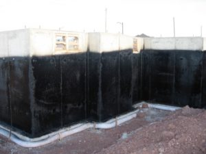 Damp-proof coating sprayed onto newly constructed foundation walls